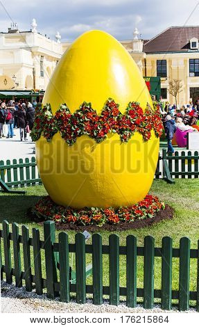 Vienna, Austria - April 3, 2015: Large yellow decorated Easter egg at the Easter market in Vienna and people buying Easter souvenirs