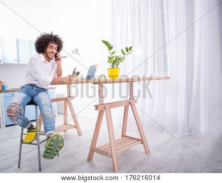Hipster freelance man talking over mobile or smart phone while working upon business projects at home alone. Business or freelance concept.