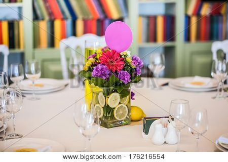 Guest table decorated with gaudy bouquet, which is in vase vith lemons