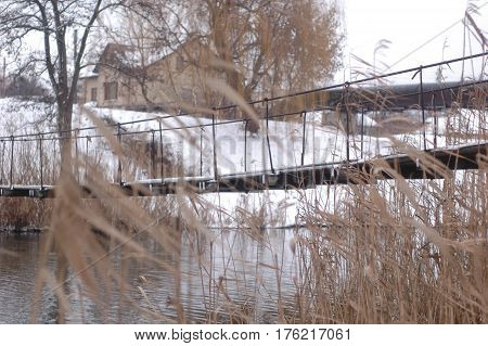 Suspension bridge over a small river against the background of reeds and snow-covered shores.
