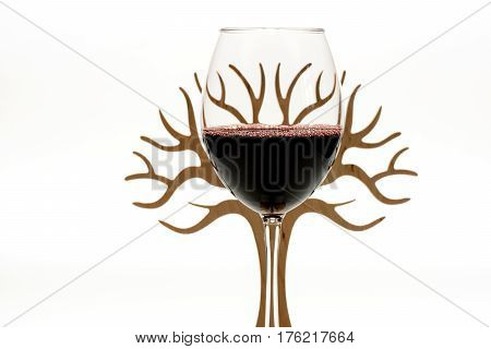 Glass of tasty dark red wine ahead of decorative wooden tree isolated on white background