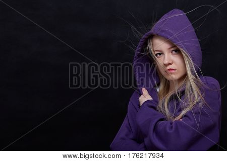 scared girl in hood looking at camera on black background