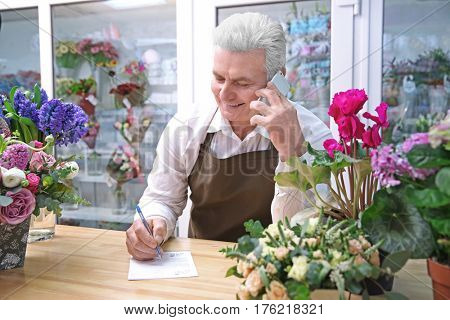 Male florist using mobile phone while writing on paper in flower shop