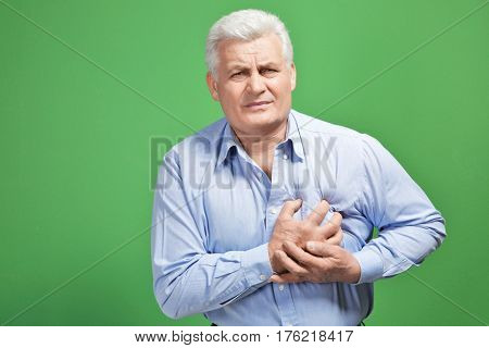 Man with chest pain suffering from heart attack on color background