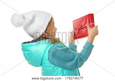 Cute little girl in warm clothes with giftbox on white background