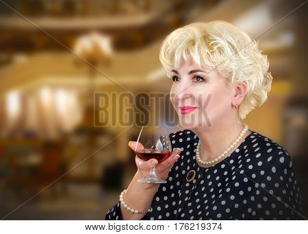 Gorgeous adult woman posing with glass of brandy. Blonde hair lady wears polka dot suit pearl necklace and bracelet.  Mid-shot on blurred interior background