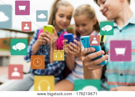 primary education, friendship, childhood, technology and people concept - group of happy elementary school students with smartphones and backpacks outdoors over multimedia icons