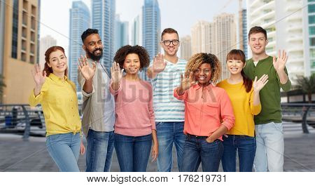 travel, tourism, diversity and people concept - international group of happy smiling men and women waving hand over dubai city street background