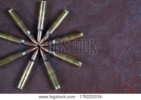 Group of  ammunition geometrically placed. Ammo circle on a rusted metal background