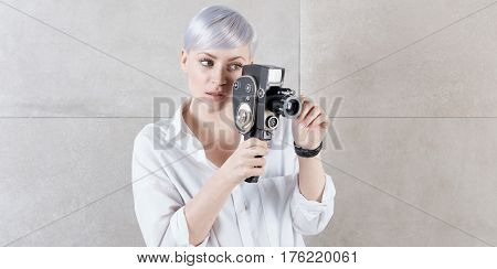Young woman holding retro movie camera.