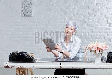 Young woman using tablet computer, sitting at desk in retro styled office.