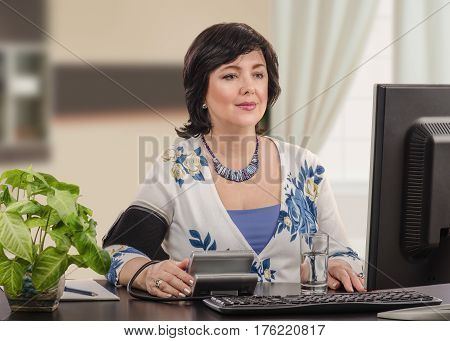 Portrait of photogenic mature businesswoman has just posted her blood pressure information to telemedicine headquarter. She sits at black desk and looks at the monitor. She waits response. Horizontal shot on blurred interior background