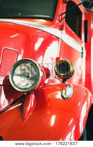 Headlight of an old red fire truck.