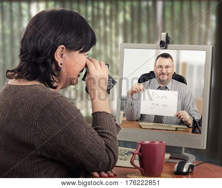 Female patient is extremely worried at first meeting with telemedicine psychotherapist. Mature woman is crying in front of computer monitor. Confident male psychiatrist shows written message Do not give up. Telepsychiatry concept. Horizontal mid-shot on b