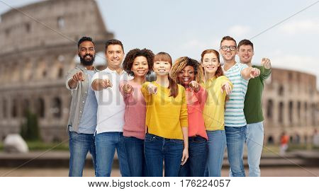 travel, tourism, diversity, choice and people concept - international group of happy smiling men and women pointing finger on you over coliseum background