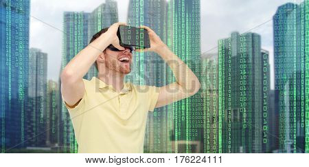 modern technology, cyberspace, entertainment and people concept - happy young man with virtual reality headset or 3d glasses over city skyscrapers and binary code background