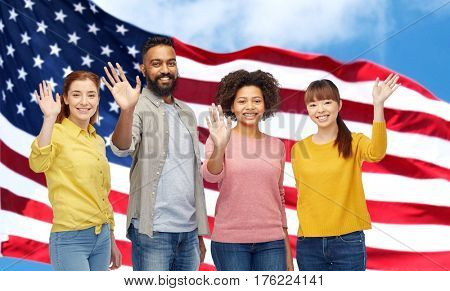 diversity, immigration and people concept - international group of happy smiling men and women waving hands over american flag background