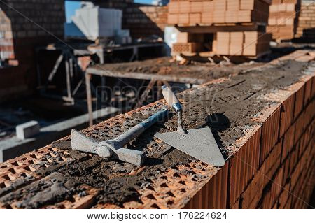 Construction tools on red bricks. Building trowel and pickaxe on the construction site. Brickwork