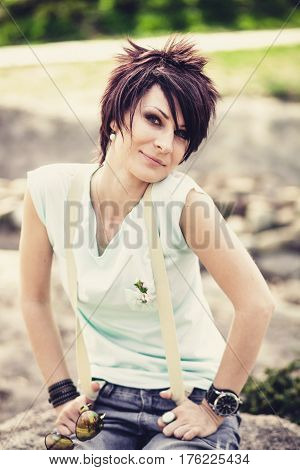Young beautiful woman with short hair sitting on a stone. Spring. Romantic style