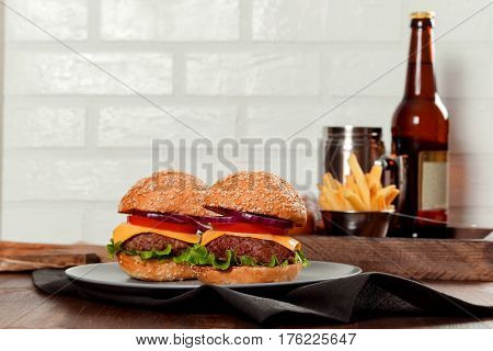 Cheeseburgers on wooden table with copy space filmed in studio