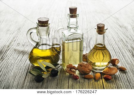 Olive walnut and almond oil on wooden background