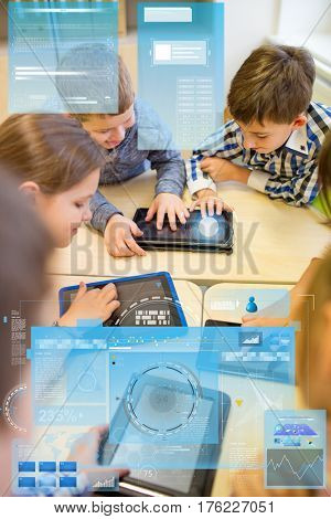 education, elementary school, learning, technology and people concept - group of kids with tablet pc computer having fun on break in classroom and virtual screen projection
