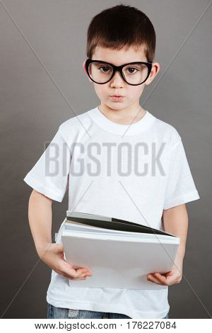 Portrait of serious little boy in glasses with blank magazine over grey background