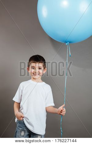 Cheerful little boy standing and holding blue balloon over grey background