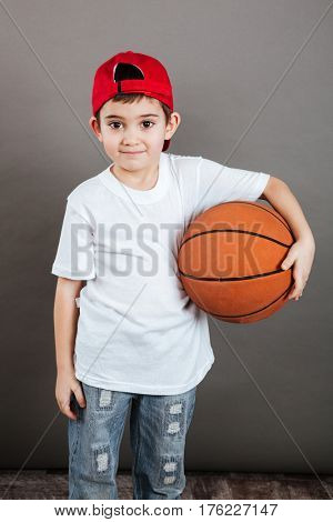 Happy little boy in cap standing and holding basketball ball over grey background