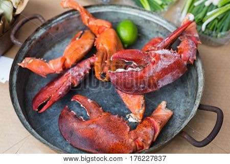 Fresh grilled lobcter claws at grill pan. Seafood delicacy barbecue outdoors. Picnic healthy food, lobster pieces in shells cooked at large metallic pan with lime. Mediterranean cuisine