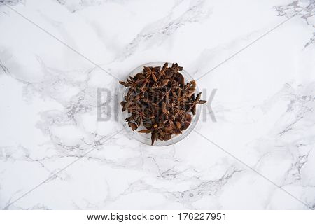 Chinese star anise or badiam seeds in a bowl on white marble table