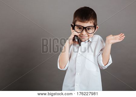 Confused little boy in glasses talking on cell phone and holding copyspace on palm over grey background