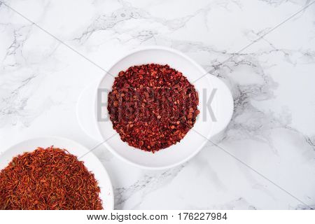 Top view of dried saffron and chilli pepper in bowls isolated on white marble table