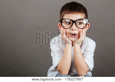 Surprised little boy in glasses sitting with hands on cheeks over grey background