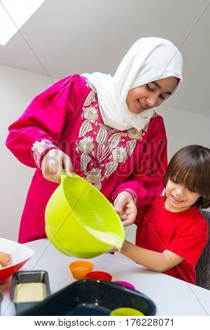 Playful fun time in kitchen with kid making muffins