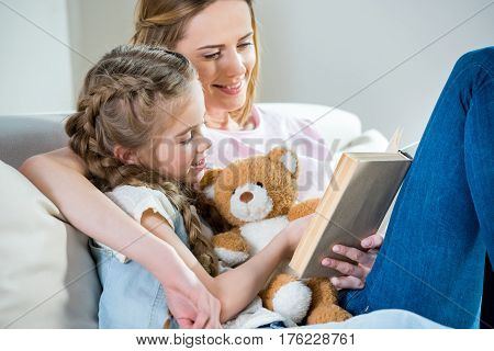 Smiling Mother And Daughter With Teddy Bear Reading Book On Sofa