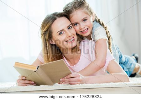 Mother And Daughter Hugging While Reading Book And Smiling At Camera