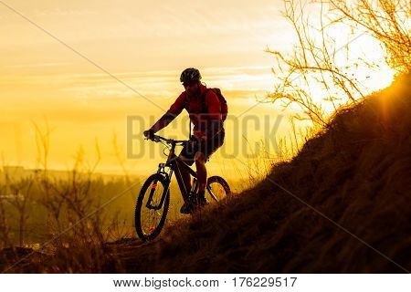 Silhouette of Enduro Cyclist Riding the Mountain Bike on the Rocky Trail at Sunset. Active Lifestyle Concept. Free Space for Text.
