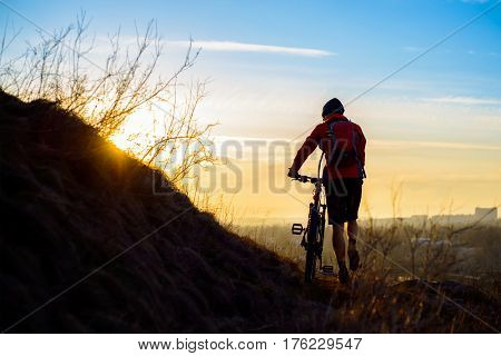 Silhouette of Enduro Cyclist with Mountain Bike on the Rocky Trail at Sunset. Active Lifestyle Concept. Free Space for Text.