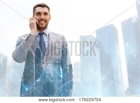 business, technology and people concept - smiling businessman calling on smartphone over city and office buildings with charts background
