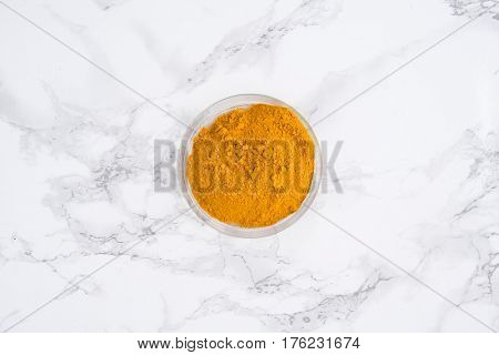 Top view of a turmeric powder in a bowl on white marble table
