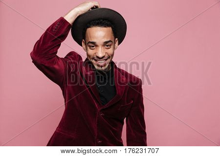 Portrait of a happy afro american man in stylish cloth posing isolated on the pink background
