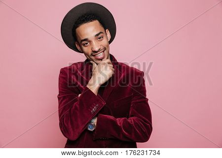 Portrait of a thoughtful afro american man in hat holding hand in his chin and looking at camera isolated on the pink background