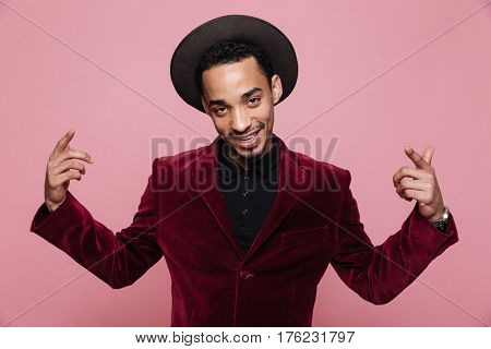 Portrait of a handsome young afro american man in jacket and hat pointing fingers isolated on the pink background