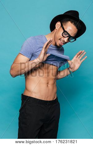 Smiling casual afro american man demonstrating his fit muscular body isolated on the blue background