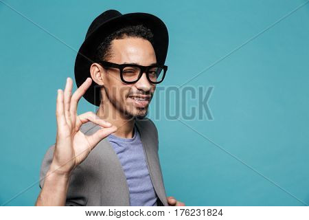 Portrait of a young afro american man in hat winking and showing okay gesture over blue background