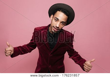 Portrait of a stylish afro american man in hat and jacket showing two thumbs up isolated on the pink background