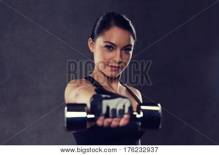 fitness, sport, exercising, training and people concept - young woman flexing muscles with dumbbells in gym