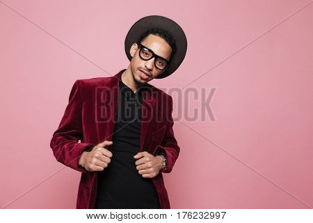 Portrait of a handsome stylish african man standing and looking at camera isolated on the pink background