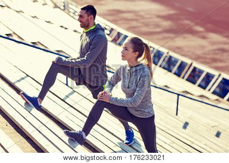fitness, sport, exercising and lifestyle concept - couple stretching leg on stands of stadium